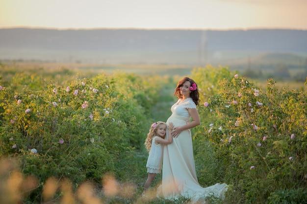 Glückliche schwangere frau mit kleiner tochter in einem rosengarten des grünen tees