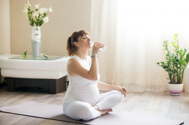 Glückliche schwangere frau trinkt natürliches wasser nach dem ausarbeiten