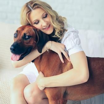 Glückliche schwangere frau und ein hund, der auf einer couch sitzt, die niedlich kuschelt