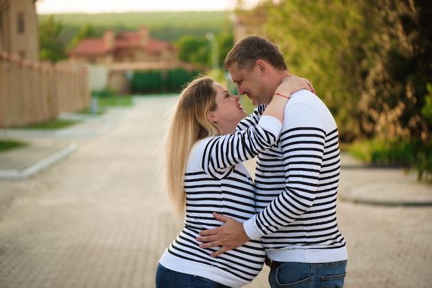 Glückliche schwangere frau und ihr ehemann, die, auf der straße aufwerfend küsst und umarmt.