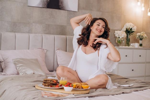 Glückliche schwangere frau zu hause auf dem bett, das frühstück isst