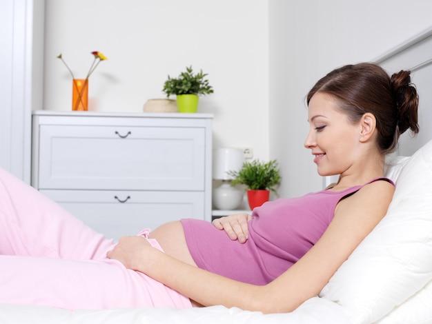 Glückliche schwangere junge frau, die auf dem bett liegt und bauch berührt