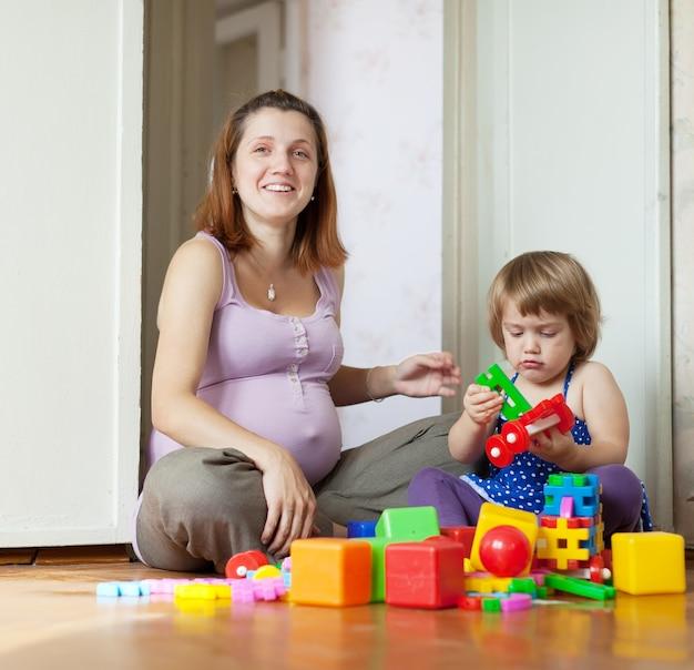 Glückliche schwangere mutter spielt mit kind