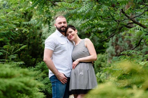 Glückliche schwangere paare draußen.
