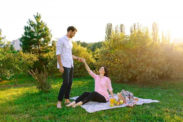 Glückliche schwangere paare im park auf picknick