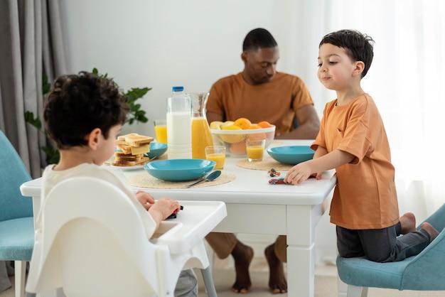 Glückliche schwarze familie, die sich zum frühstück fertig macht