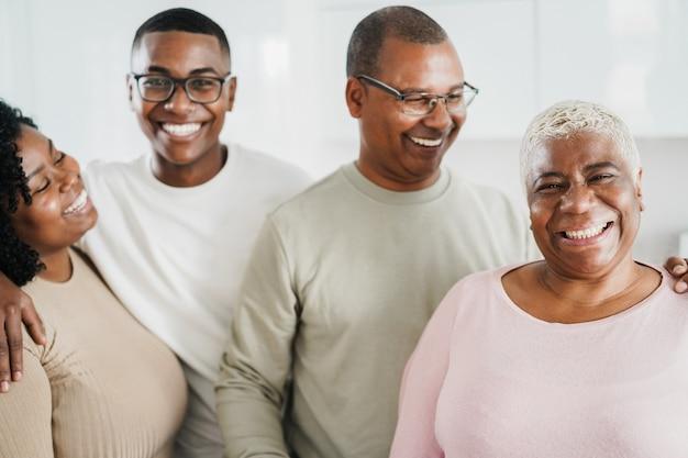 Glückliche schwarze familie, die vor kamera zu hause lächelt - fokus auf mutter