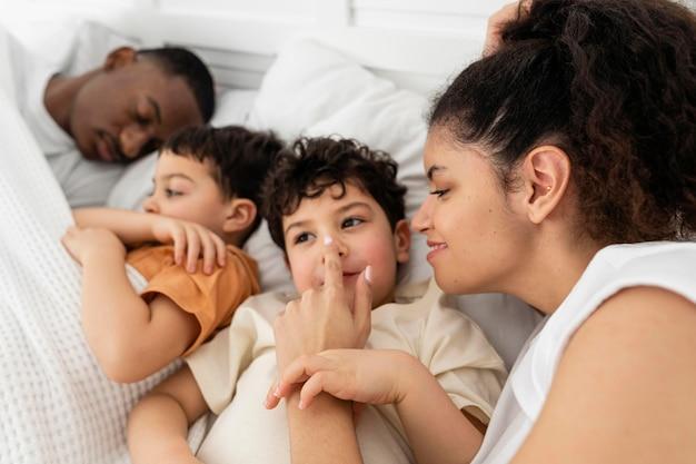 Glückliche schwarze familie, die zusammen schläft