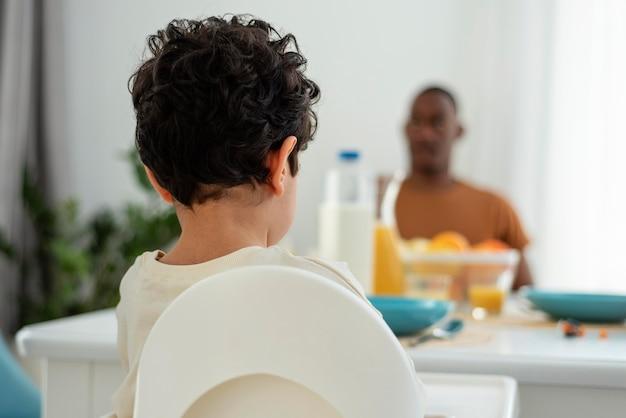 Glückliche schwarze familie mit kleinkind, das am tisch bleibt