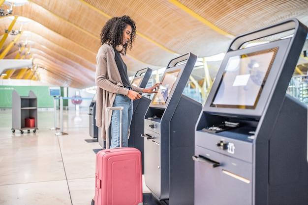 Glückliche schwarze frau, die den abfertigungsautomaten am flughafen erhält die bordkarte verwendet.