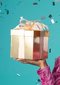 Glückliche schwarze frau, die eine geschenkbox hält