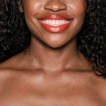 Glückliche schwarze frau, die einen pfirsichfarbenen lipgloss trägt
