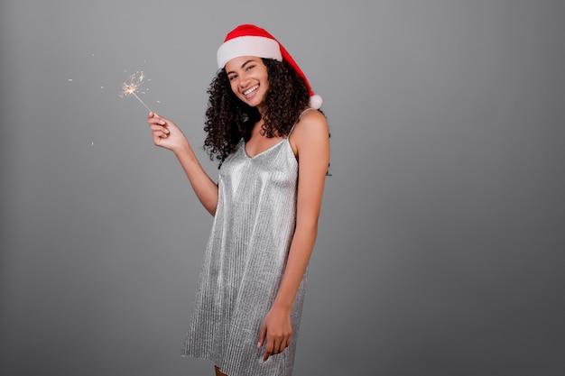 Glückliche schwarze frau mit den funkelnden wunderkerzen, die den weihnachtshut und -kleid lokalisiert über grau tragen