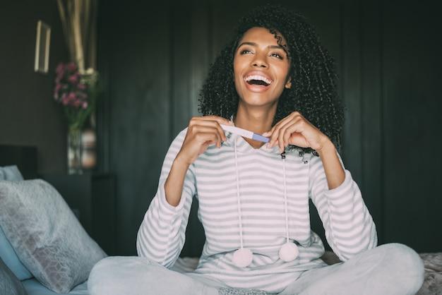 Glückliche schwarze frau mit einem schwangerschaftstest auf bett