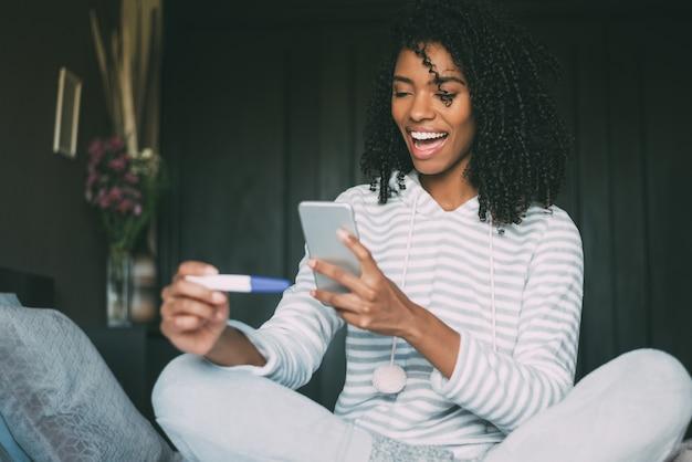 Glückliche schwarze frau mit einem schwangerschaftstest und einem smartphone auf bett