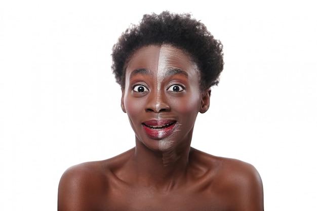 Glückliche schwarze frau mit halbem gesicht auf make-up, schönheitskonzept