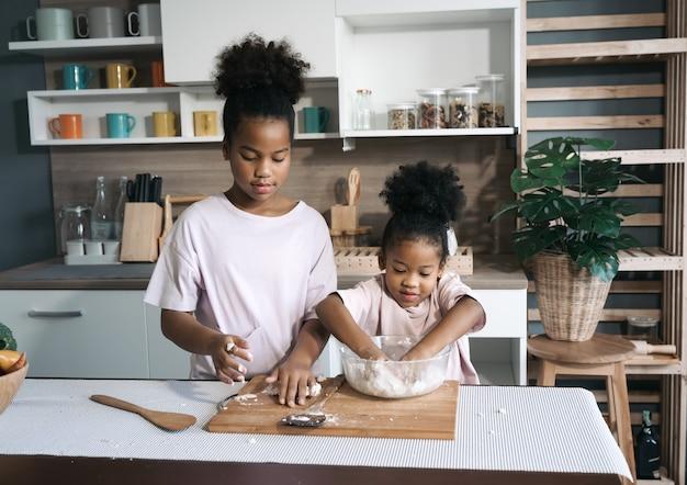 Glückliche schwarze schwestern, die mehl in der küche dreschen