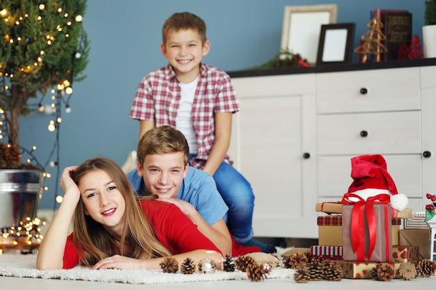 Glückliche schwester und brüder mit geschenken auf dem boden im dekorierten weihnachtsraum