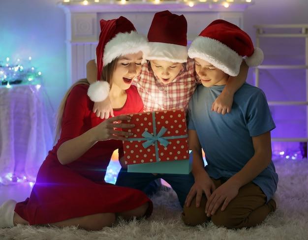 Glückliche schwester und brüder öffnen geschenkbox auf dem boden im dekorierten weihnachtsraum