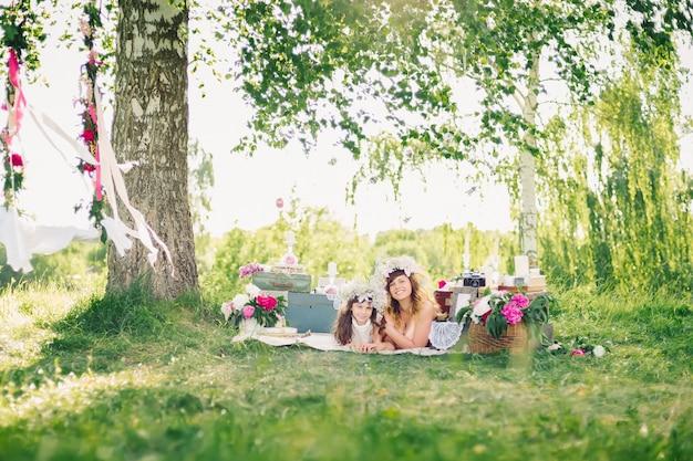 Glückliche schwestern, die draußen auf einer decke auf einem sonnigen sommer liegen