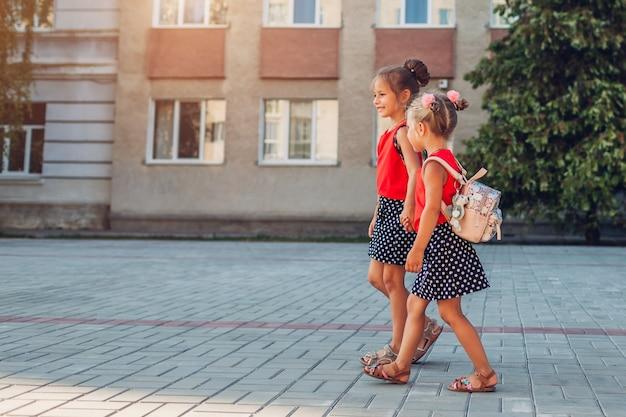 Glückliche schwestern, die rucksäcke tragen, die händchen haltend zur schule gehen. bildung. zurück zur schule