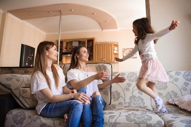 Glückliche schwestern, die spaß im wohnzimmer spielen und haben