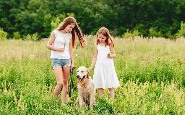 Glückliche schwestern mit niedlichem hund auf blühender sommerwiese