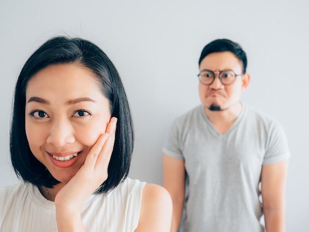 Glückliche schwierige asiatische frau und der verärgerte verliererehemann