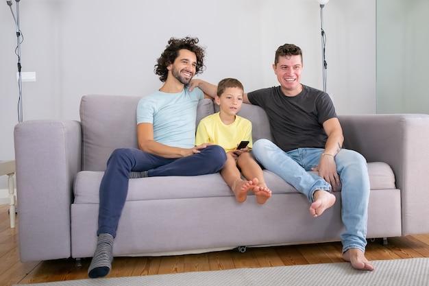 Glückliche schwule eltern und sohn sitzen zusammen auf der couch zu hause und schauen komödie im fernsehen, schauen weg, lächeln und lachen. familien- und elternschaftskonzept