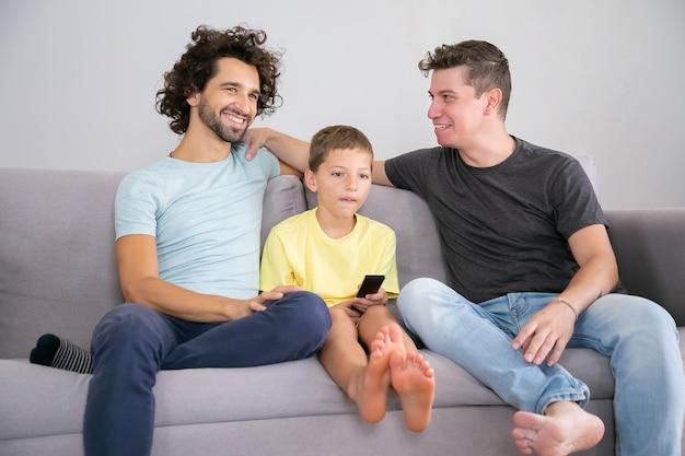 Glückliche schwule väter und sohn sitzen zusammen auf der couch zu hause, lächeln, reden und schauen weg. junge, der mit fernbedienung fernsieht. familien- und elternschaftskonzept