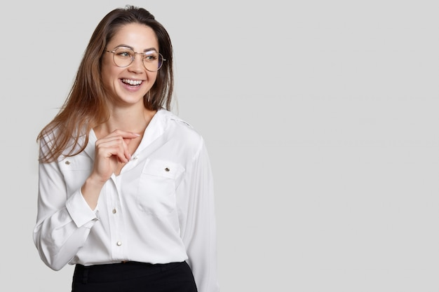 Glückliche sekretärin gekleidet in schwarzen und weißen kleidern