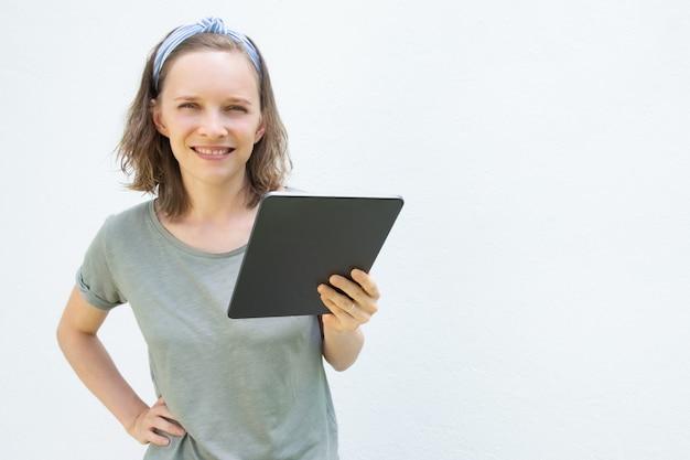 Glückliche selbstbewusste junge frau, die digitales gerät hält