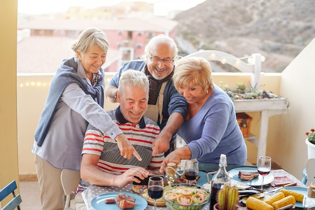 Glückliche senioren, die am intelligenten mobiltelefon am abendessen auf terrasse aufpassen