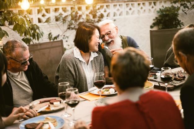 Glückliche senioren, die spaß beim grillabendessen haben