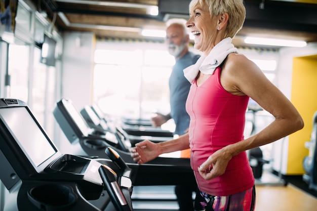 Glückliche senioren, die zusammen auf laufbändern im fitnessstudio laufen.