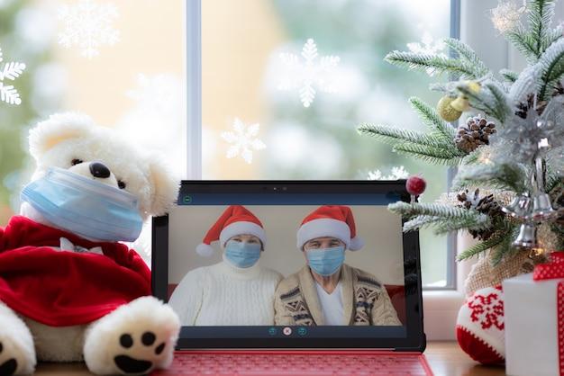 Glückliche senioren mit medizinischer maske mann und frau begrüßen im video-chat