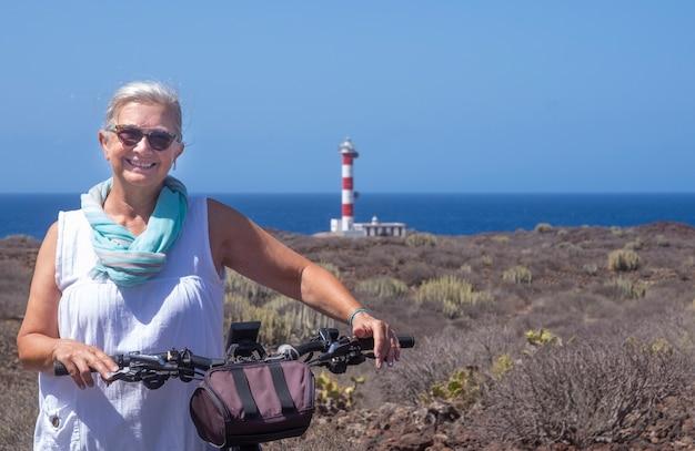 Glückliche seniorin, die freiheit und ausflug mit dem fahrrad in der nähe eines leuchtturms genießt - trockene landschaft und horizont über wasser an einem sonnigen tag auf teneriffa, kanarische inseln