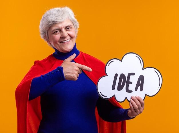 Glückliche seniorin superheldin mit rotem umhang mit sprechblasenschild mit wortidee, die mit dem zeigefinger darauf zeigt, fröhlich lächelnd