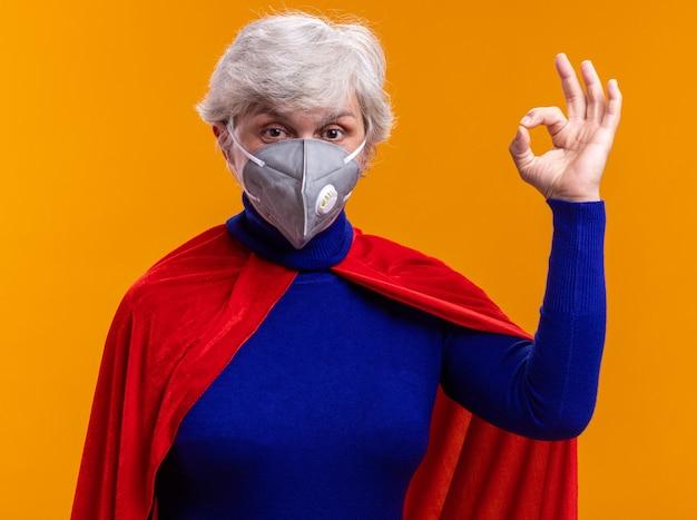 Glückliche seniorin superheldin mit rotem umhang und gesichtsschutzmaske, die auf die kamera schaut und ein ok-zeichen auf orangefarbenem hintergrund zeigt