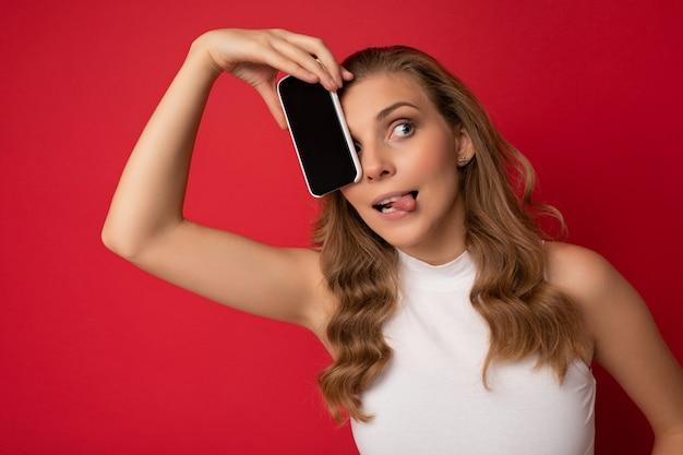Glückliche sexy attraktive junge blonde weibliche person, die weißes t-shirt lokalisiert auf rotem hintergrund trägt
