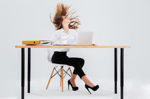Glückliche sexy junge geschäftsfrau, die am tisch mit haaren sitzt, die über weißem hintergrund in die luft fliegen