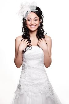 Glückliche sexy schöne braut brunettefrau im weißen hochzeitskleid mit frisur und hellem make-up