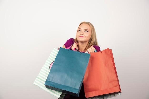 Glückliche shopaholic frau, die bunte einkaufstaschen hält. hochwertiges foto