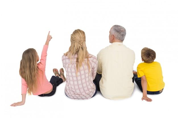 Glückliche sitzende und zeigende familie