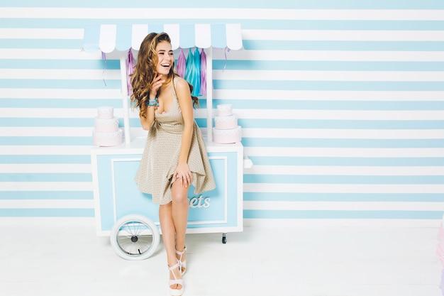 Glückliche sommerzeit des hübschen modischen modells im kleid, das spaß auf gestreifter wand hat. süßer dessert-truck, kuchen, lachen, wahre positive gefühle ausdrücken.