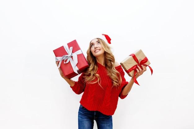 Glückliche sorglose blonde frau, die neujahrsparty hält, die geschenke hält. trägt rote weihnachtsmütze und strickpullover. posieren