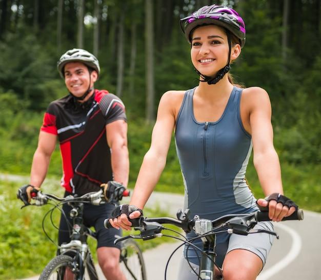 Glückliche sorglose fahrradpaare, die draußen radfahren.