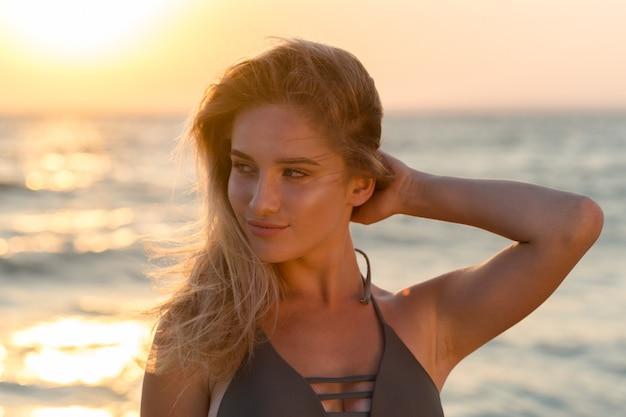 Glückliche sorglose frau auf dem strand sommer genießend