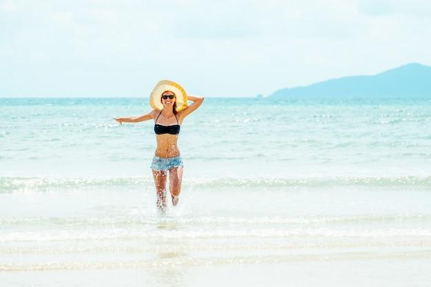 Glückliche sorglose frau, die bikini trägt, der spaß in den sommerferien hat