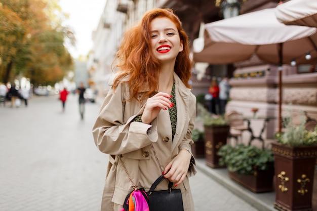 Glückliche sorglose frau mit roten haaren und hellem make-up, das auf der straße geht. beige mantel und grünes kleid tragen.
